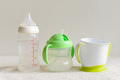 Three kinds of bottles and cups with water for baby.