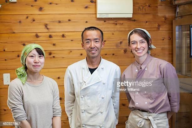 Three kitchen staff together in a kitchen