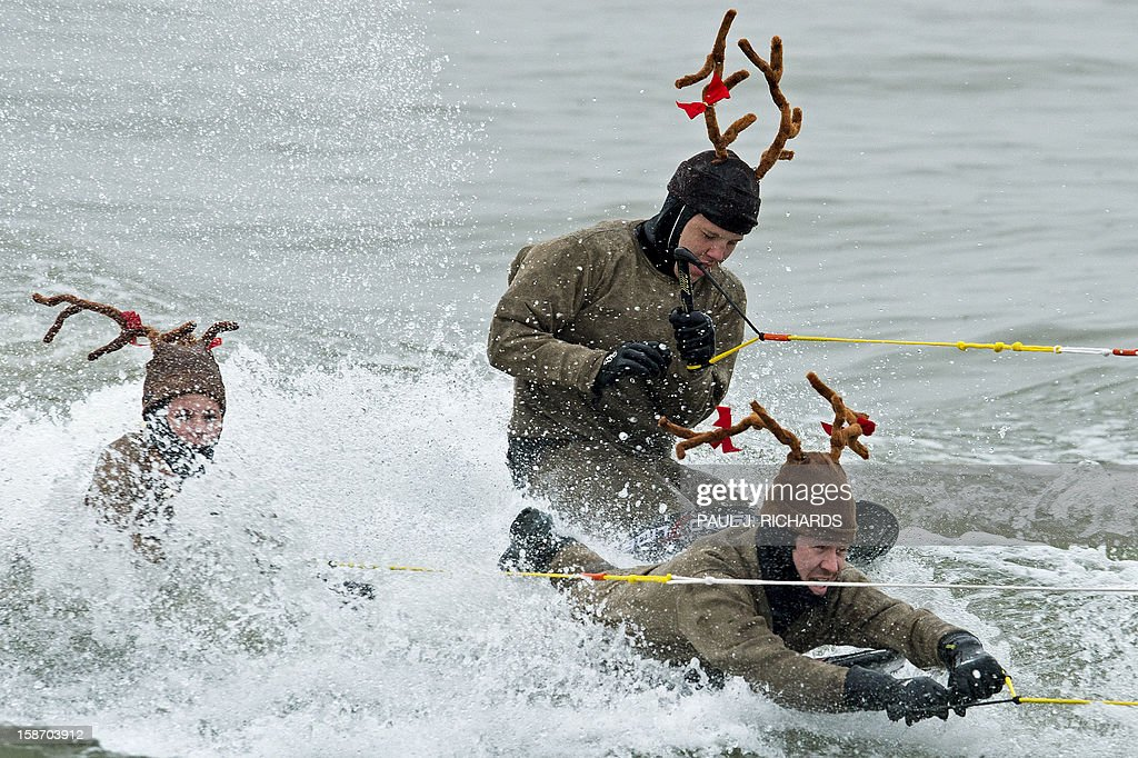 Three knee-boarding reindeer ride on the Potomac River at National Harbor in Maryland near Washington, DC, December 24, 2012 as part of the Water-Skiing Santa Show. This unusual annual event features a water-skiing Santa, flying elves, the Jet-skiing Grinch, and Frosty the Snowman performing on the Potomac River. AFP PHOTO/Paul J. Richards