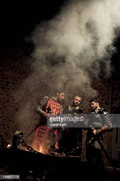 Tres knights alrededor de fuego con chalices brindis