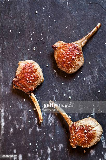 Three lamb chops and sea salt on slate