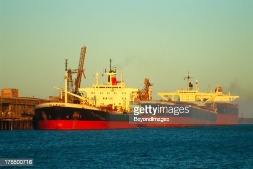 Three large ships loading iron ore at sunset