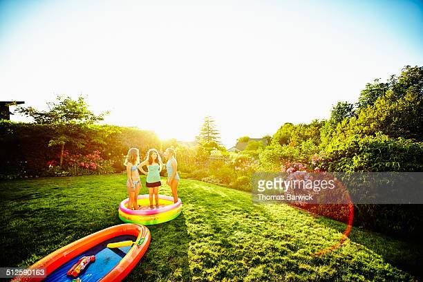 Three laughing young girls in inflatable pool