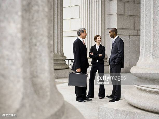 Three lawyers talking in front of a courthouse