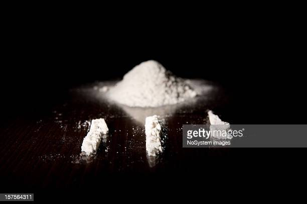 Three lines of cocaine next to a pile of it