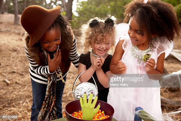 Three little girls in Halloween costumes laughing.