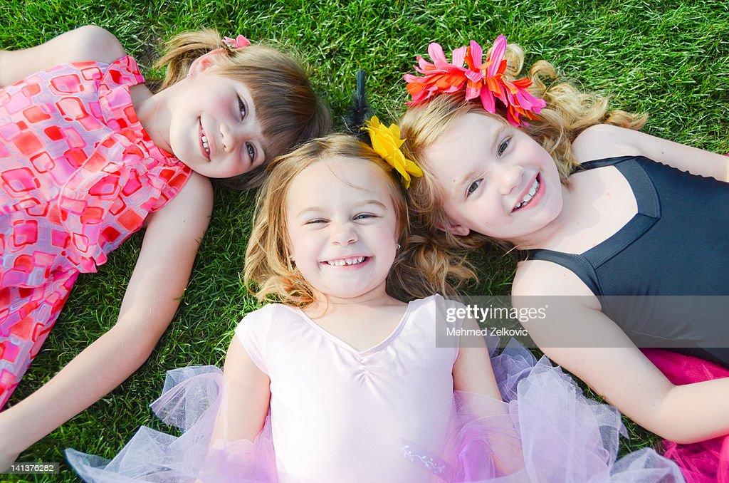 Three little girls on grass : Stock Photo