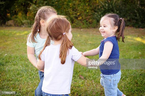 Tre bambine giocano Girotondo
