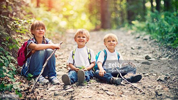 Three little hikers sitting on the forest path