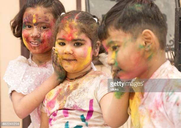 Three little kid celebrating holi