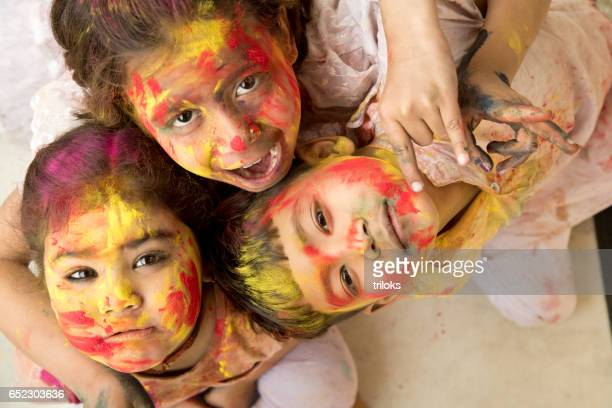 Three little kid painted their face with multi colors