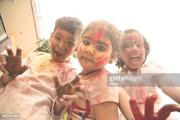 Three little kid playing with colors