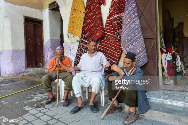 Three locals having a chat in one of many small streets inside Fes Medina A scene from a daily life in Fes during the Ramadan 2017 On Saturday June...
