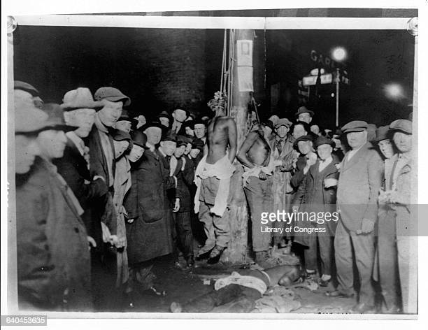 A crowd of Caucasian men surround two African American men hanging from nooses on a pole with their shirts torn down to their waists