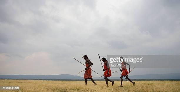 Three Maasai Warriors Running Across Savannah