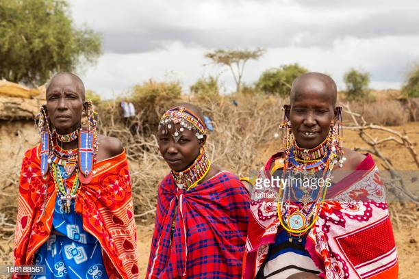 Three Maasai women outside their village.