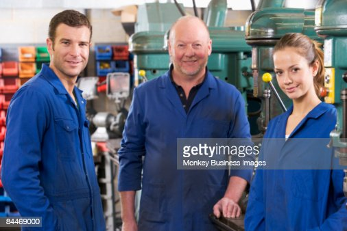 Three machinists in workspace by machine talking : Photo