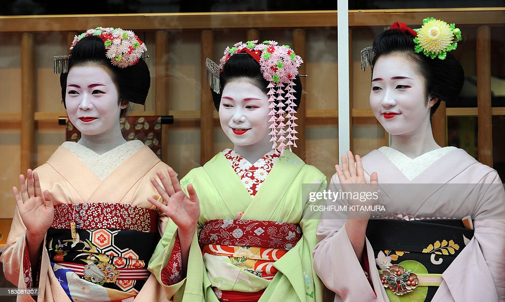 Three 'Maikos,' or apprentice geishas, (L-R) Ichitomi, 18, from Gion Kobu, Toshitomo, 16, from Miyagawa cho and Chizu, 20, from Ponto cho wave while attending the 'We're alive and well, Kyoto' campaign in Tokyo on October 4, 2013. As Kyoto prepares itself for the biggest sightseeing season of autumn, the girls lent their charms to lure back tourists to the 1,200-year-old city after a big typhoon flooded some of scenic spots there three weeks ago. AFP PHOTO / TOSHIFUMI KITAMURA