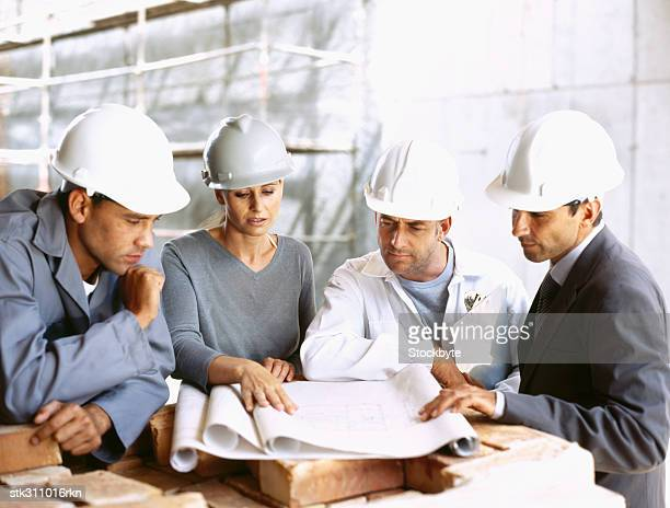 three male architects and a female architect discussing a blueprint