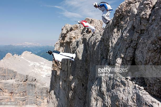 Three male BASE jumpers exiting from mountain top, Dolomites, Italy