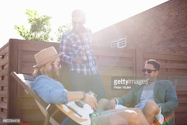 Three male friends chatting and playing guitar at rooftop party