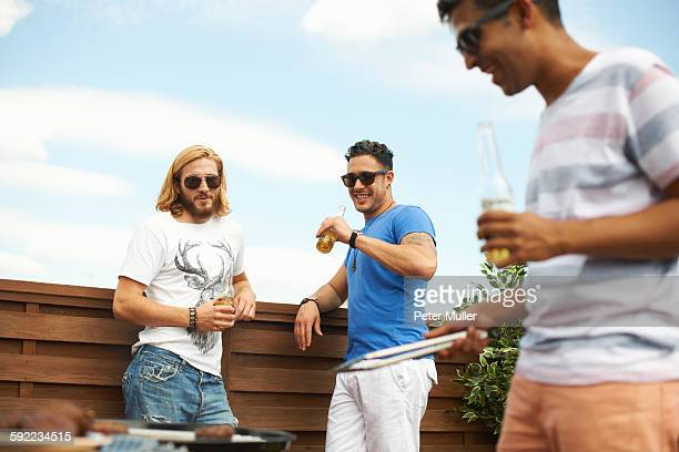 Three male friends drinking beer and barbecuing at rooftop barbecue