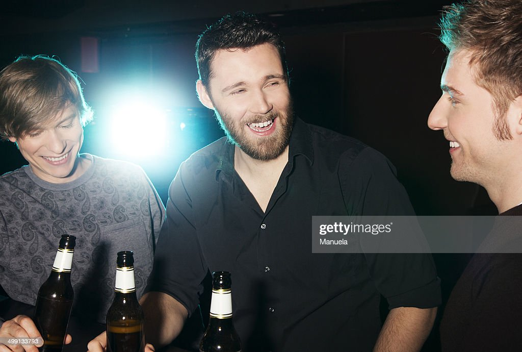 Three male friends drinking bottled beer in nightclub