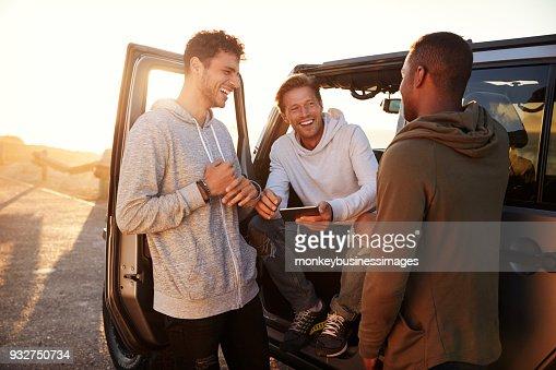 Trois amis de sexe masculin sur un road trip à l'aide d'une tablette PC : Photo