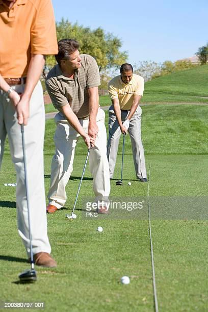 Three male golfers hitting golf balls at driving range