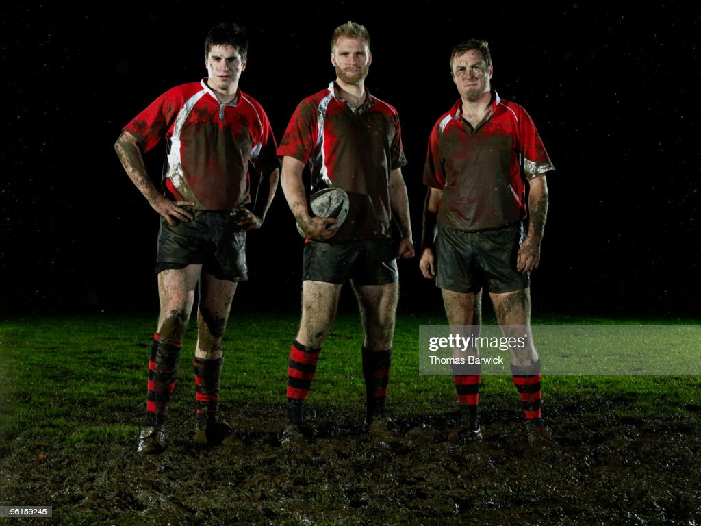 Three male rugby players covered in mud : Stock Photo