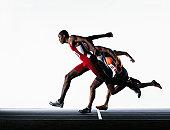 Three male runners crossing finish line