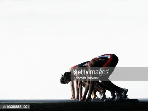 Three male runners in starting blocks, side view : Stock Photo