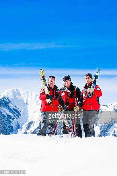 Three male ski patrollers on slope, smiling, portrait