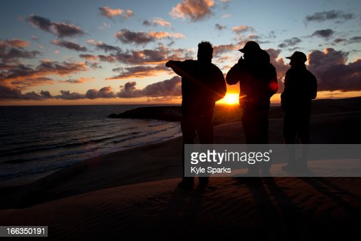 Three male surfers check the surf conditions at sunset during a surf trip in Central Baja, Mexico.