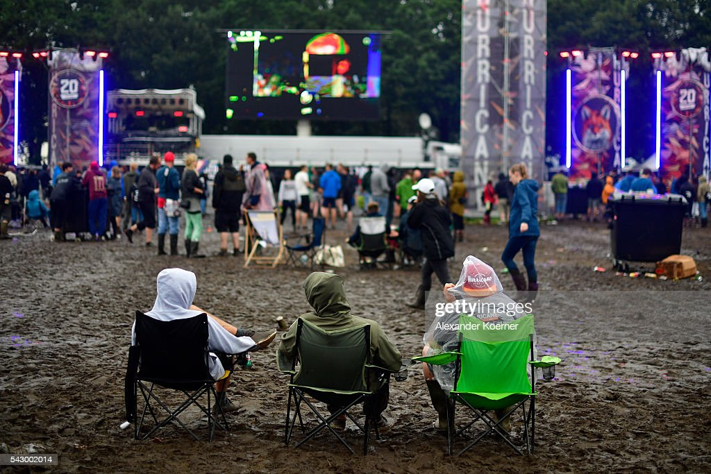Three male visitors sit on chair at the muddy camping compound at the Hurricane Festival compound on June 25, 2016 in Scheessel, Germany. The Hurricane Festival was evacuated yesterday and was delayed today for the late evening, following heavy rain and thunderstorm alerts. The rain and thunderstorm have hit the festival during the night and day, causing damage to tents and flooded the festival site, only 7 concerts can be played on two stages today. The Hurricane Festival celebrates this year its 25th anniversary. 75.000 music fans have visited the Festival, but some thousands have already left the compound due to the current situation.