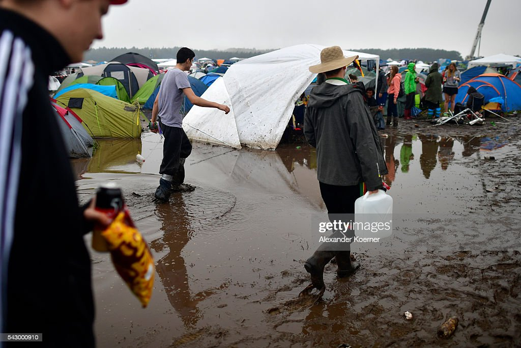 Three male visitors walk through a puddle at the camping compound at the Hurricane Festival compound on June 25, 2016 in Scheessel, Germany. The Hurricane Festival was evacuated yesterday and was delayed today for the late evening, following heavy rain and thunderstorm alerts. The rain and thunderstorm have hit the festival during the night and day, causing damage to tents and flooded the festival site, only 7 concerts can be played on two stages today. The Hurricane Festival celebrates this year its 25th anniversary. 75.000 music fans have visited the Festival, but some thousands have already left the compound due to the current situation.