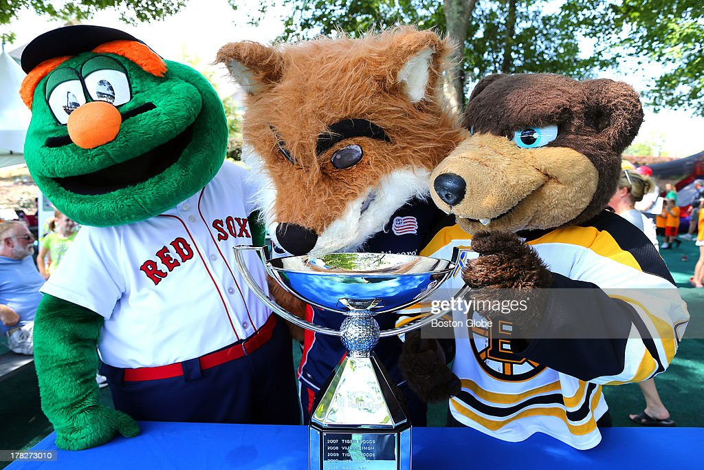 Three mascots pondered drinking out of the FedEx Cup in the children's play area. Boston Red Sox's Wally, New England Revolution's Slyde, and Boston Bruins's Blades entertained kids during the day. Practice took place at the TPC Boston for the Deutsche Bank Championship, Aug. 28, 2013.