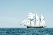 Three mast schooner under sails on the baltic sea. Cross processed.