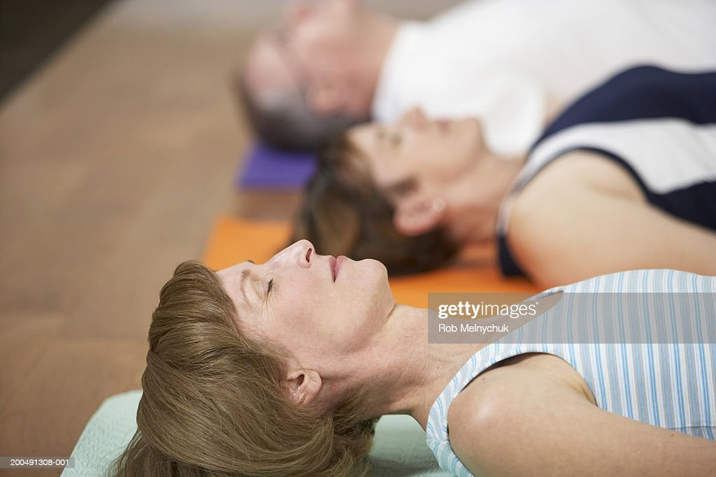 Three mature adults in yoga class (focus on woman lying in foreground) : Stock Photo