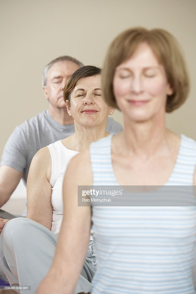 Three mature adults meditating in yoga class, eyes closed : Stock Photo