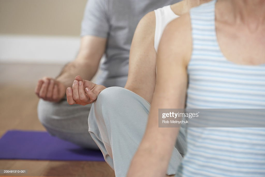 Three mature adults meditating in yoga class, mid section : Stock Photo