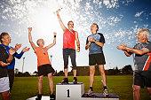 Three mature athletes on podium with medals