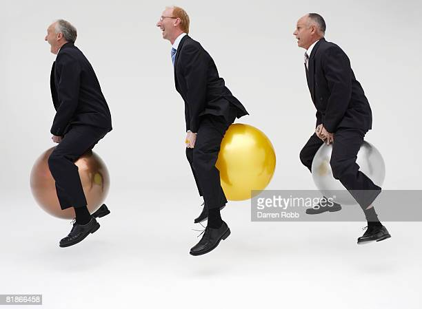 Three mature businessmen bouncing on Space Hoppers