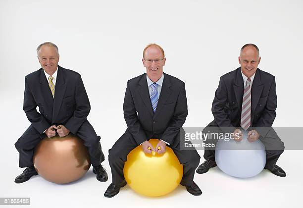 Three mature businessmen sitting on Bronze, Silver and Gold inflatable space hoppers, smiling