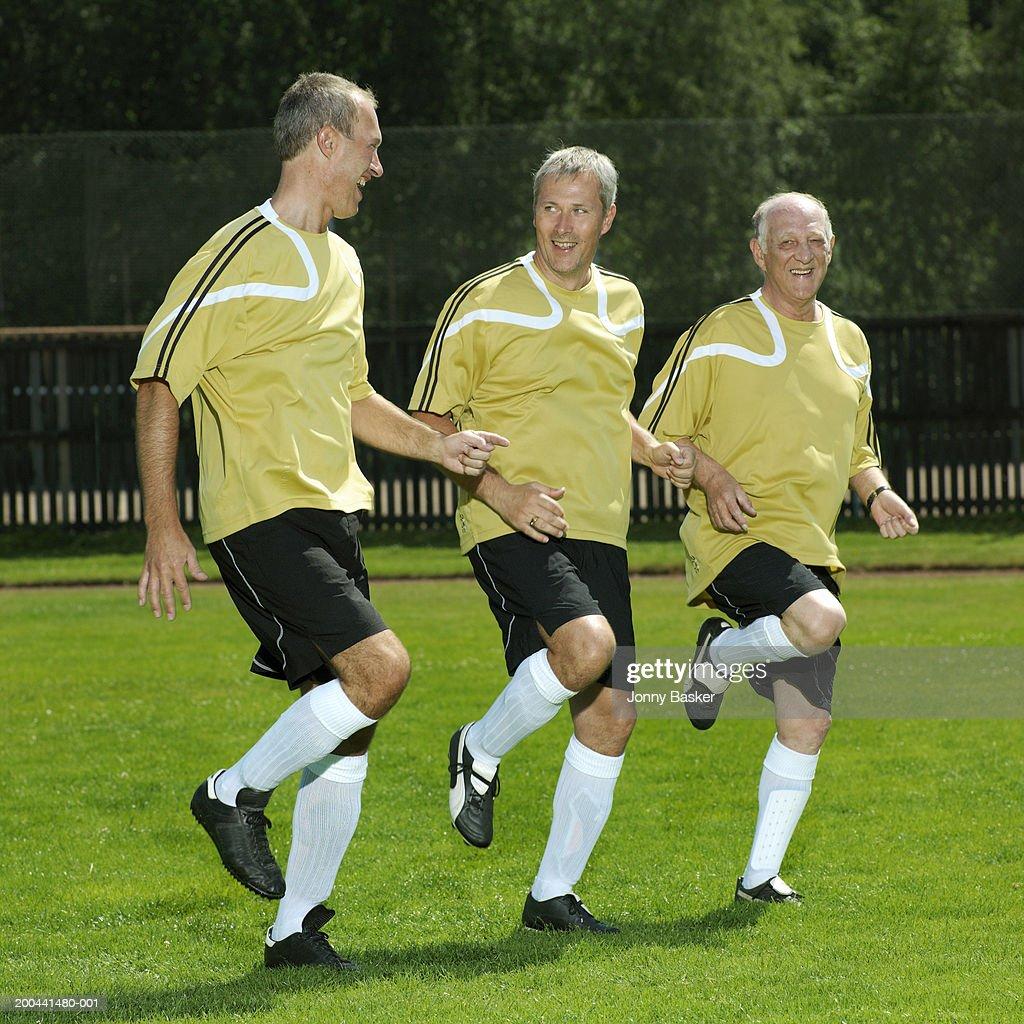 Three mature football players warming up