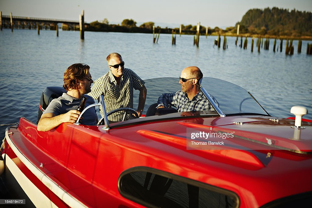 Three mature male friends hanging out in boat : Stock Photo