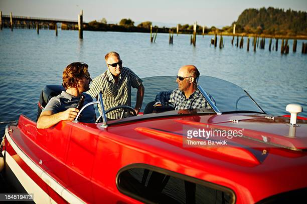 Three mature male friends hanging out in boat