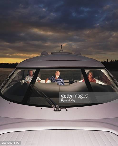 Three mature men at helm of yacht, view through window