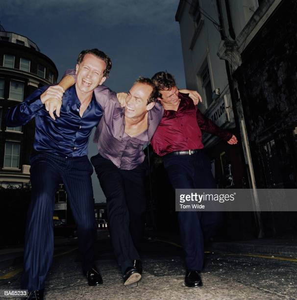 Three mature men stumbling along street supporting each other
