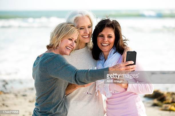 Three mature women at the beach taking selfie